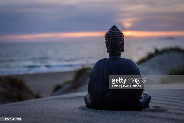 buddha sitting i the sand. dunes and ocean in the background. sunset with beautiful colors over the ocean. buddha to the right - finn bjurvoll ストックフォトと画像