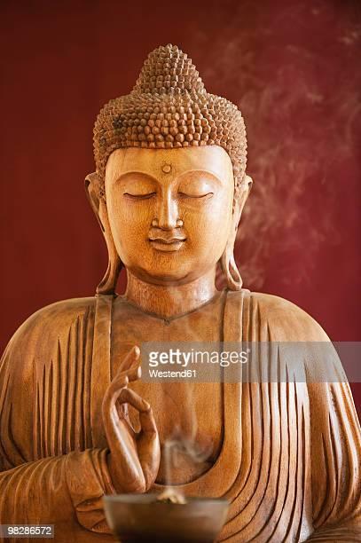 Buddha statue and a bowl with joss sticks