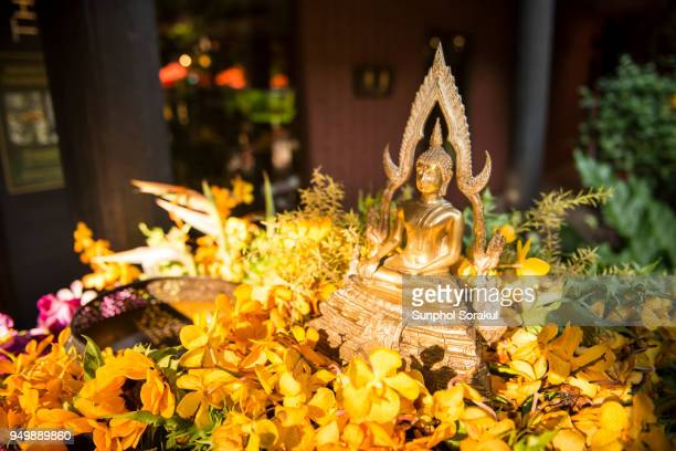 Buddha statue and flowers for bathing ritual during Songkran festival