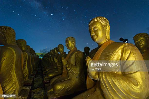buddha statue and night sky with milky way