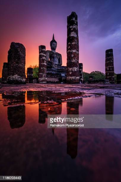 buddha statue and temple ruins in sunset in sukhothai, thailand - sukhothai stockfoto's en -beelden