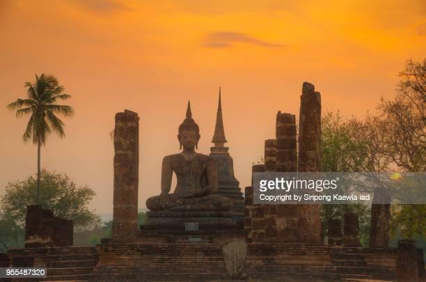 buddha statue at wat mahathat inside the sukhothai historical park at sunset, sukhothai province, thailand. - sukhothai stockfoto's en -beelden