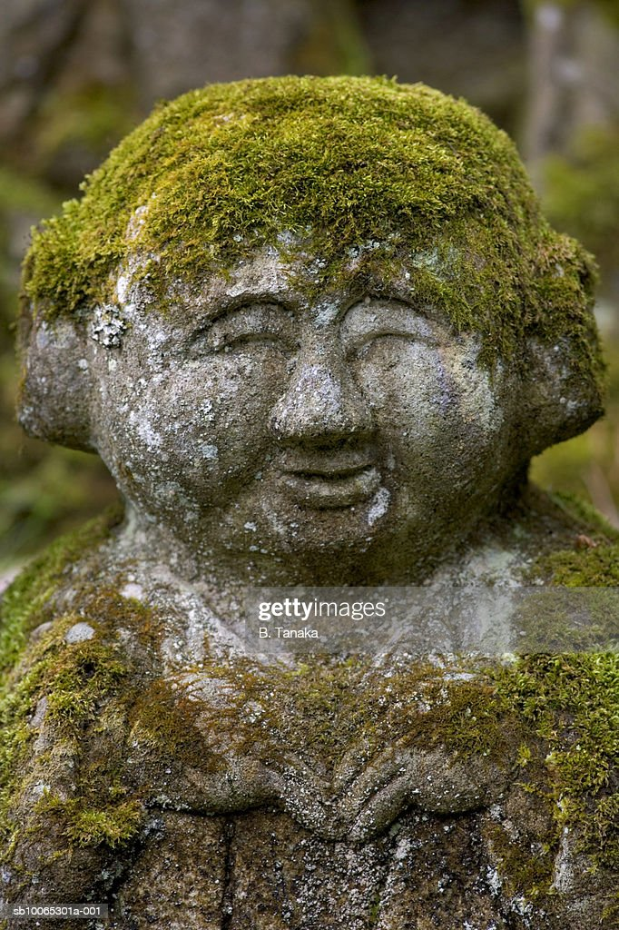 Buddha statue covered with green moss, close-up : Foto stock