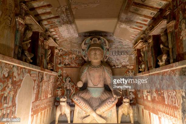 Buddha statue in the cave, surrounded with ancient colorful murals. The Mogao Caves, also known as the Thousand Buddha Grottoes, are the best known...