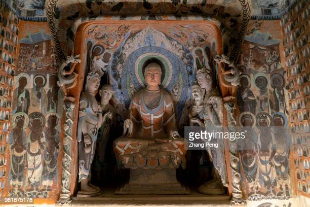 Buddha statue in the cave surrounded with ancient colorful murals The Mogao Caves also known as the Thousand Buddha Grottoes are the best known of...