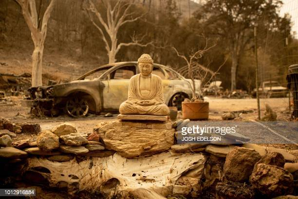 A Buddha statue is seen at a burned home in Spring Valley near Clearlake Oaks northern California on August 7 2018 Tens of thousands of firefighters...