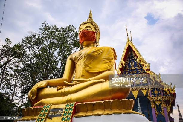 Buddha statue of Nidharat Pradit temple wears a face mask to encourage people to use facial coverings as a preventive measure against the spread of...