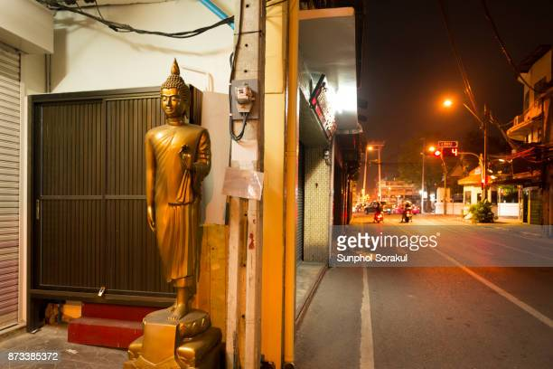 A Buddha statue on the street with Giant swing in the background