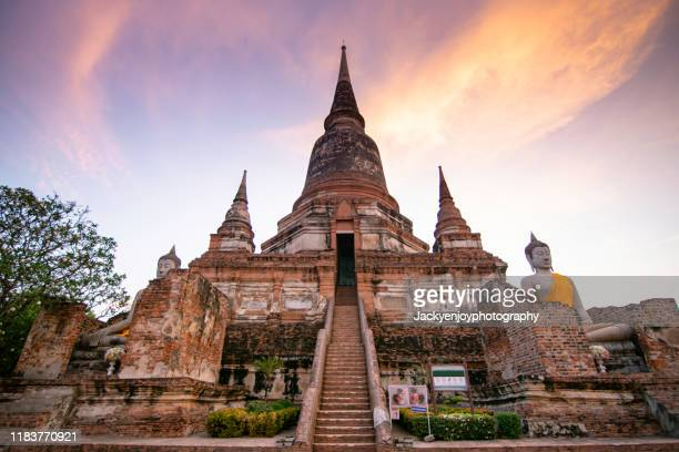 buddha statue with a tall chedi in the center of wat yai chaya mongkol in ayutthaya thailand. it is one of the famous landmark to see in this ancient city. - ayuthaya province stock pictures, royalty-free photos & images
