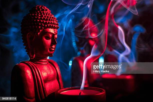 buddha statue with candle - incense stock photos and pictures