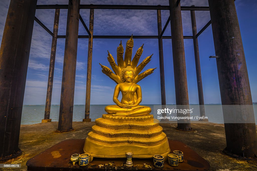 Buddha Statue With Paint Cans On Pier Against Sky : Stock Photo