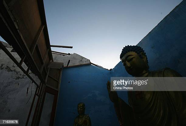 Buddha statues are seen at a collapsed temple after typhoon Saomai landed at Dongdianbao Village on August 12 2006 in Cangnan County of Zhejiang...