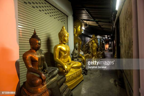 Buddha statues on pavement in a small alleyway Bangkok, Thailand