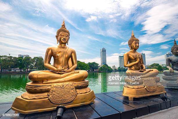 Buddha Statues On Retaining Wall By Lake Against Sky