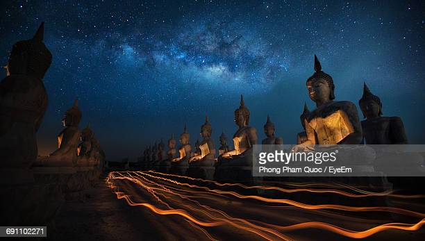 buddha statues under star field - buddha stock pictures, royalty-free photos & images