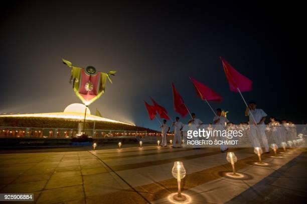 Buddhism followers carry lit candles after evening prayers to mark Makha Bucha Day at Wat Phra Dhammakaya temple near Bangkok on March 1 2018 Makha...