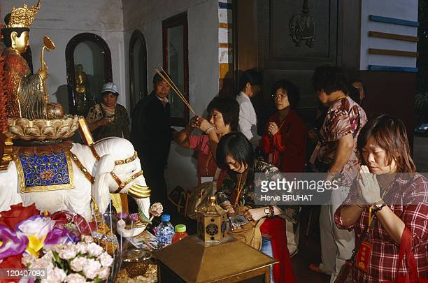 Buddhism in China Emei mountain Sichuan province Pilgrims visiting Wannian Temple They are worshipping the bodhisattva Puxian riding a white elephant