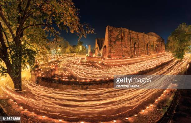 Buddhism light waving rite walk with lighted candles in hand around on Vesak day at Temple in Ayutthaya , Thailand