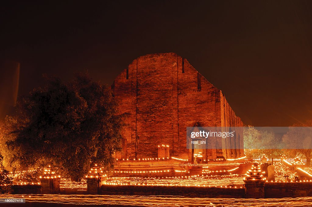 Buddhism walk with lighted candles trail around ancient temple : Stock Photo