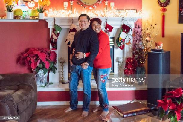 buddhist couple embracing in living room decorated for christmas - stockings no shoes stock pictures, royalty-free photos & images
