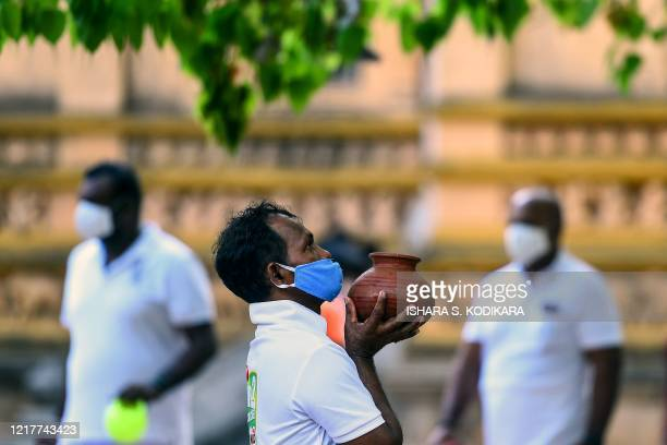A Buddhist devotee holds a pot of water while offering prayers at the Kelaniya temple during the Poson Poya religious festival marking the arrival of...