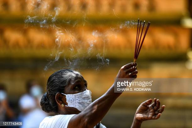 A Buddhist devotee holds incenses at the Kelaniya temple during the Poson Poya religious festival marking the arrival of Buddhism in the island on...