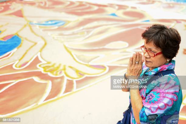 Buddhist devotee prays next to a 25-year-old, 196-foot-long sacred 'Thangka' during the Wesak day or Buddha Day festival celebrations at the...