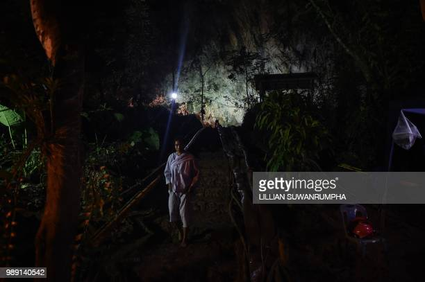 Buddhist devotee walks down from the mouth of Tham Luang cave at the Khun Nam Nang Non Forest Park in Chiang Rai province on July 2 as the rescue...