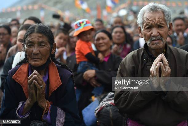 Buddhist devotees folds their hands after the Tibetan spiritual leader the Dalai Lama arrives for his teachings at the 'Degon Yarchos Chenmo 2017' at...