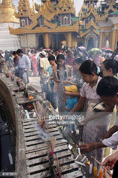 Buddhist devotees light candles and incense at Shwedagon Pagoda in downtown Yangon on July 17 2008 to mark the day when Buddha delivered his first...