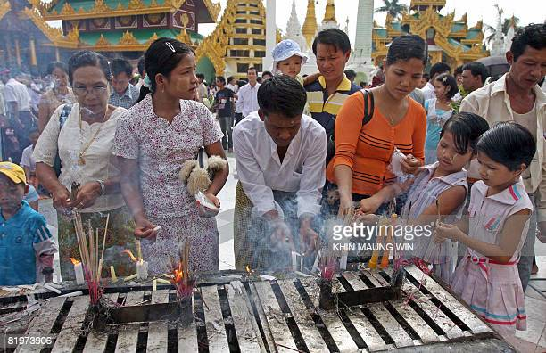 Buddhist devotees light candles at Shwedagon Pagoda in downtown Yangon on July 17 2008 to mark the day when Buddha delivered his first sermon...