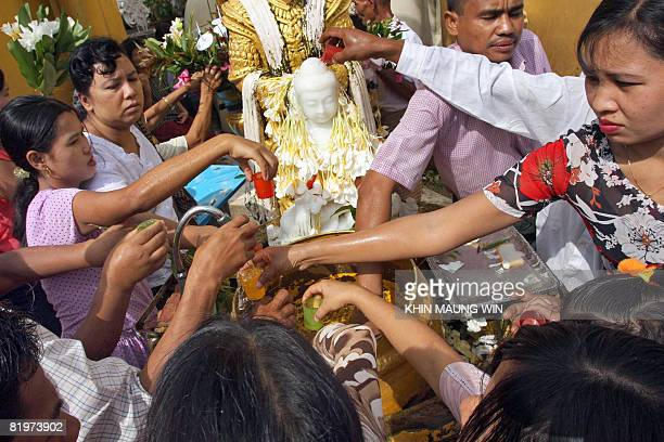 Buddhist devotees pour water on a Buddhist statue at Shwedagon Pagoda in downtown Yangon on July 17 2008 to mark the day when Buddha delivered his...