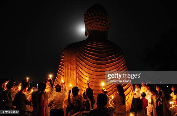 Buddhist devotees trying to click pictures of full moon with Buddha on the occasion of Buddha Purnima at a monastery on May 3 2015 in Bhopal India...