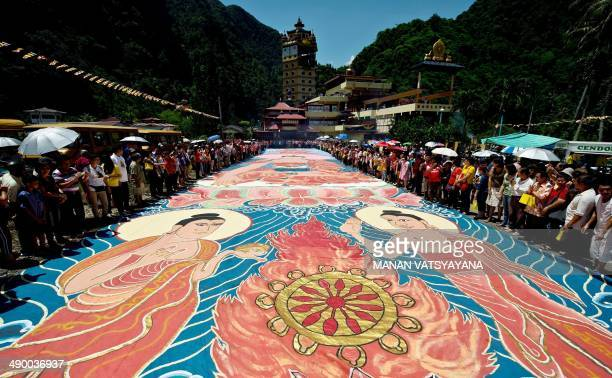 Buddhist devotees unfurl the 22 yearold 196 footlong sacred 'Thangka' under the sun during Wesak day celebrations at a Tibetan Buddhist temple in...