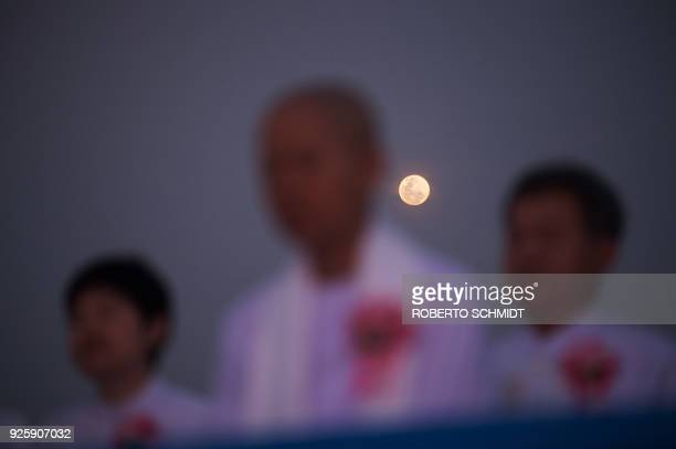 Buddhist faithful pray while the full moon rises behind them during Makha Bucha Day celebrations at Wat Phra Dhammakaya temple near Bangkok on March...