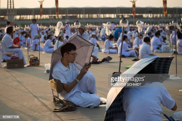 A buddhist faithful sits under an umbrella as he waits among others for the beginning of the evening prayers during Makha Bucha Day celebrations at...