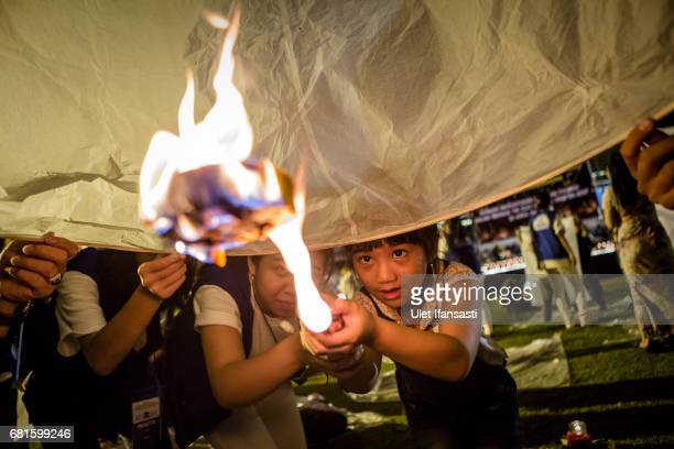 Buddhist follower girl light a lantern as they prepare release lanterns into the air on Borobudur temple during celebrations for Vesak Day on May 10...