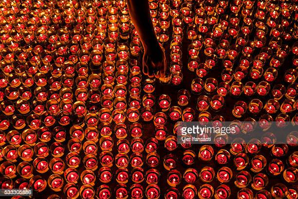 A buddhist follower light candles at the Borobudur temple during celebrations for Vesak Day on May 22 2016 in Magelang Central Java Indonesia Vesak...