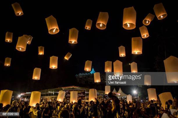 Buddhist followers and tourists release lanterns into the air on Borobudur temple during celebrations for Vesak Day on May 10 2017 in Magelang...