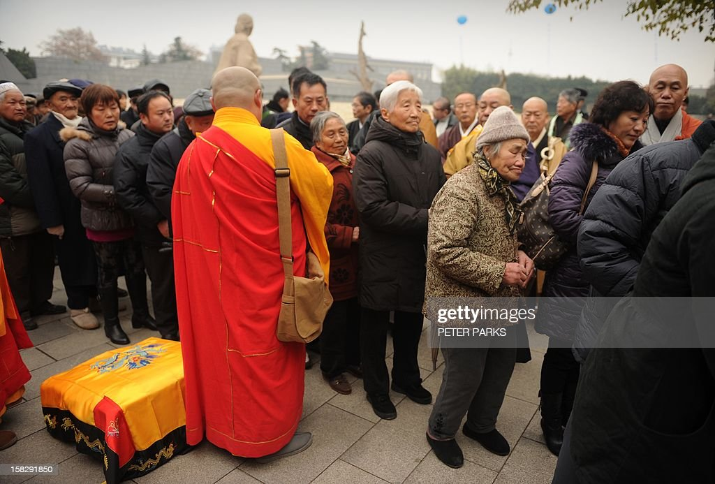 A Buddhist monk (C) blesses Nanjing massacre survivors and their relatives as they pay their respects to victims on the 75th anniversary of the Nanjing massacre at the Memorial Museum in Nanjing on December 13, 2012. Air raid sirens sounded in the Chinese city of Nanjing on December 13 as it marked the 75th anniversary of the mass killing and rape committed there by Japanese soldiers -- with the Asian powers' ties at a deep low. AFP PHOTO/Peter PARKS