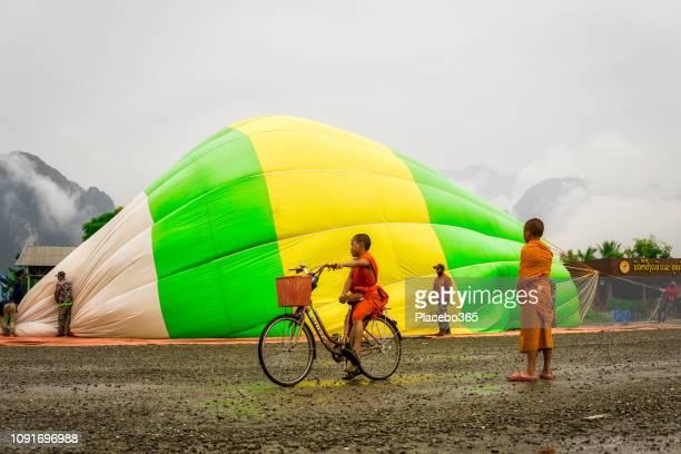 Buddhist Monk children cycling near hot air balloon
