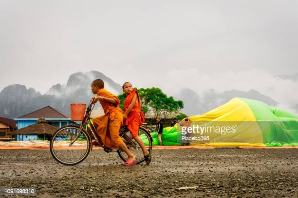 niños de monje budista ciclismo cerca de globo de aire caliente - laos fotografías e imágenes de stock