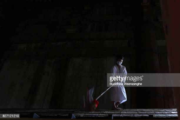 Buddhist monk cleans the dust off of 'Daibutsu' or the Great Buddha and inside the temple during the annual cleaning annual cleaning at Todaiji...