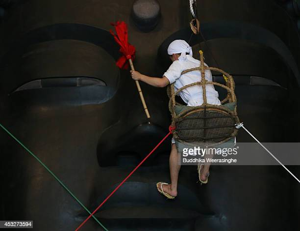 Buddhist monk cleans the dust off of the 15meterhigh Great Buddha at the Todaiji Temple on August 7 2014 in Nara Japan About 100 Buddhist monks take...