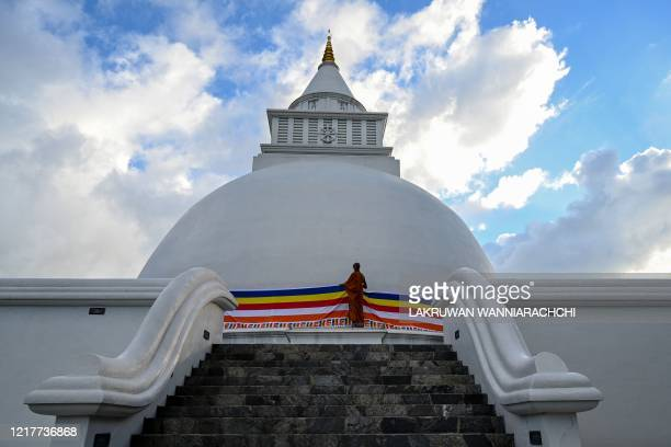 Buddhist monk drapes a Buddhist flag around the stupa in Sri Vidyashanthi Temple in Colombo on June 5 during the Poson Poya religious festival Sri...