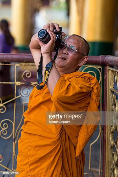 buddhist monk framing a photograph - merten snijders stockfoto's en -beelden