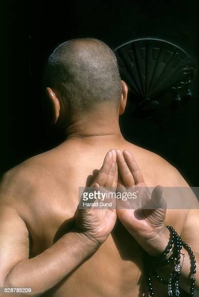 Buddhist monk, hands, prayer beads behind back