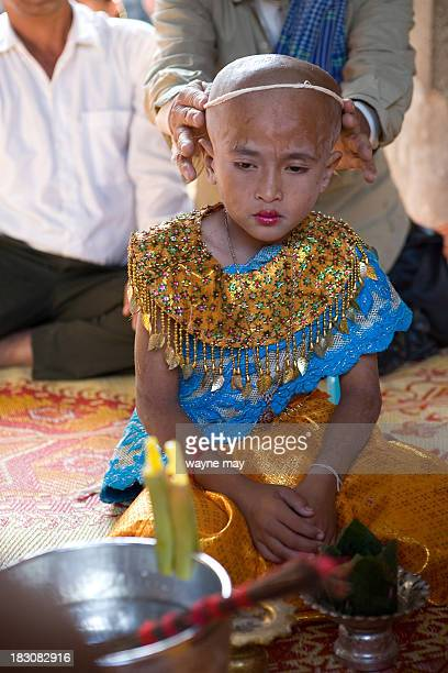 Buddhist monk has just shaved the head of a young boy, preparing him for a ceremony to be ordained as a novice Buddhist monk, in Siem Reap . Although...