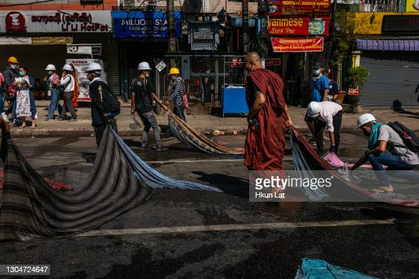 Buddhist monk helps anti-coup protesters clean up an area after a crackdown by riot police on March 01, 2021 in Yangon, Myanmar. Myanmar's military...