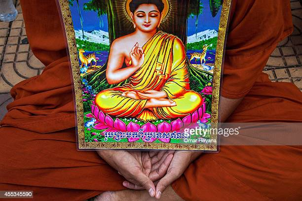Buddhist monk holds a painting of Buddha during a hunger strike in Freedom Park on September 13 2014 in Phnom Penh Cambodia A planned hunger strike...